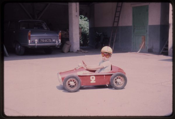 Retro child racing driver in miniature racing car at Hotel de France